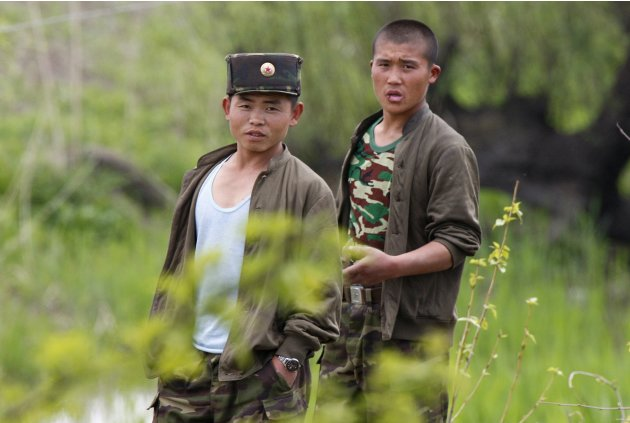 North Korean soldiers look at a Chinese tourist boat as they work on Hwanggumpyong Island, located in the middle of the Yalu River, near the North Korean town of Sinuiju