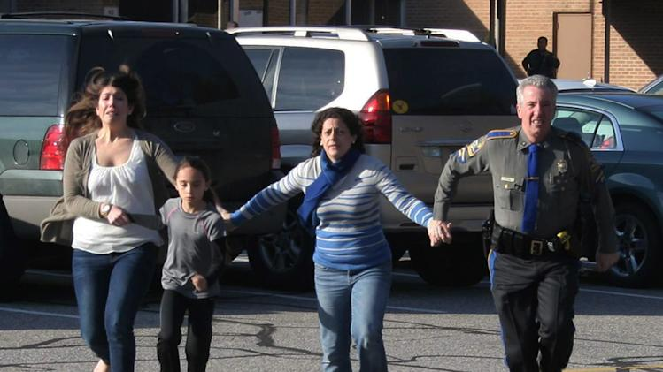 FILE - In this Dec. 14, 2012 file photo provided by the Newtown Bee, a police officer leads two women and a child from Sandy Hook Elementary School in Newtown, Conn., shortly after Adam Lanza opened fire, killing 26 people, including 20 children. State's Attorney Stephen Sedensky III asked a judge in Danbury Superior Court, Wednesday, March 27, 2013 to limit the information to be made public from warrants in Newtown school shooting, due to be released Thursday. (AP Photo/Newtown Bee, Shannon Hicks, File) MANDATORY CREDIT: NEWTOWN BEE, SHANNON HICKS