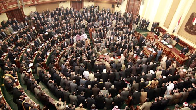 "FILE - In this Monday, Jan. 23, 2012 file photo, members of parliament stand and pray for the souls of the victims who died during the uprising that ousted President Hosni Mubarak during the first Egyptian parliament session after the revolution, in Cairo, Egypt. Egypt's highest court has ordered the country's Islamist-dominated parliament dissolved, saying its election about six months ago was unconstitutional. The Supreme constitutional Court ruled Thursday that a third of the legislature was elected illegally. As a result, it says in its explanation of the ruling, ""the makeup of the entire chamber is illegal and, consequently, it does not legally stand."" (AP Photo/Asmaa Waguih,Pool, File)"