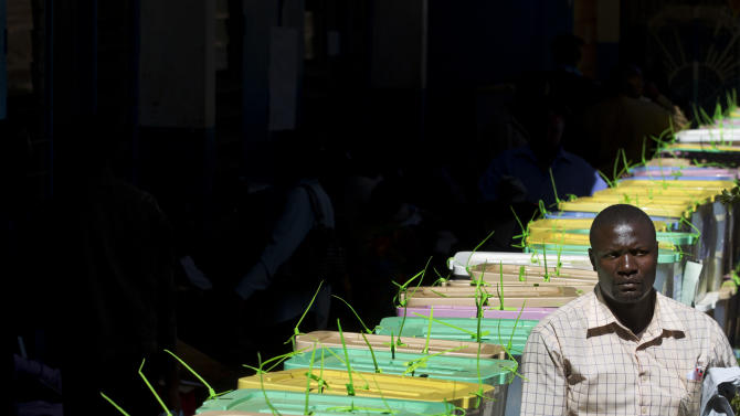 "An unidentified man walks past stacked ballot boxes waiting to have their votes tallied, at a vote tallying center in Nairobi, Kenya Tuesday, March 5, 2013. A slow ballot count in Kenya's presidential election raised questions Tuesday about the election process, but it was the more than 325,000 ""spoiled ballots"" that emerged as a potentially bigger issue. (AP Photo/Ben Curtis)"
