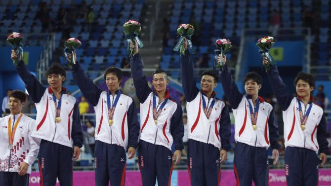 Members of Japan's men's gymnastics team celebrate after winning the gold medal for the team gymnastic competition during the 17th Asian Games in Incheon