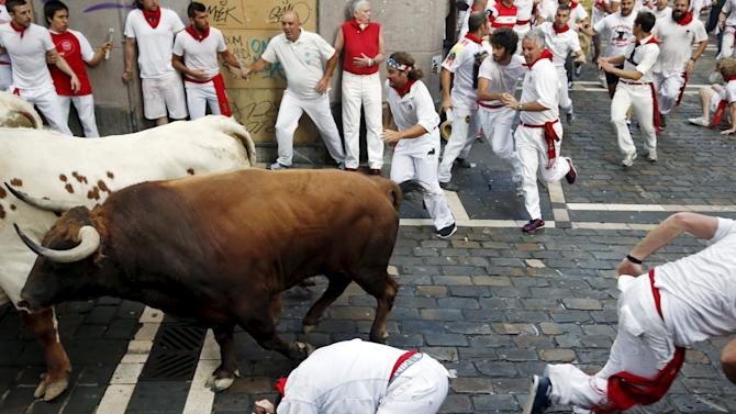 A runner falls next to a Jandilla fighting bull at the Mercaderes curve during the first running of the bulls of the San Fermin festival in Pamplona