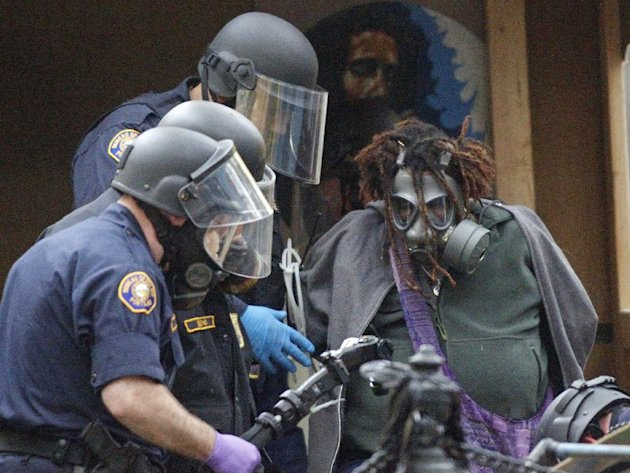 "Police officers arrests a protester in the Portland encampment Sunday, Nov. 13, 2011, in, Portland, Ore. In a tense escalation of the Occupy Portland protest, police in riot gear Sunday surrounded demonstrators in a downtown park area after hundreds of people defied the mayor's order to leave the park by midnight. By early afternoon, officers had mostly surrounded the camp where the protesters were holding a ""general assembly"" meeting to discuss their next moves following the eviction order. (AP Photo/Rick Bowmer)"