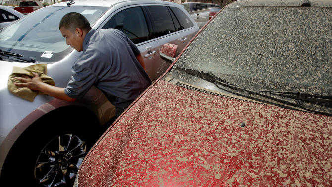 Jonathan Murguia, a recon manager for a local car dealership, cleans a washed car as a dirty car sits next to him, a locals scramble to clean up in the aftermath of a massive dust storm Wednesday, July 6, 2011, in Scottsdale, Ariz.    The huge dust wall that crossed the metro Phoenix area Tuesday night drastically reduced visibility, halting all flights coming in and out of Phoenix Sky Harbor Airport until conditions improved.  (AP Photo/Ross D. Franklin)