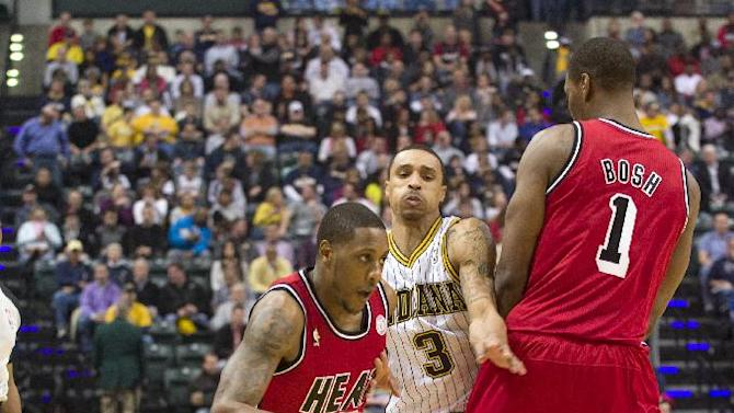 Miami Heat's Mario Chalmers (15), left, takes the ball toward the basket after using a pick set by teammate Chris Bosh (1) to beat Indiana Pacers' George Hill (3) during the first half of an NBA basketball game in Indianapolis, Friday, Feb. 1, 2013. (AP Photo/Doug McSchooler)