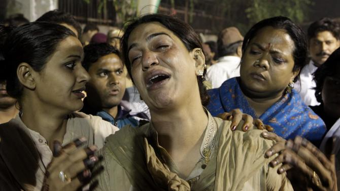 A eunuch cries as others console her at the site of fire which tore through a makeshift tent during a gathering of some thousands of eunuchs in New Delhi, India,  Sunday, Nov. 20, 2011.  The fire tore through the gathering of thousands of eunuchs in the Indian capital on Sunday, killing at least 13 people and injuring dozens of others, police said. (AP Photo/ Manish Swarup)