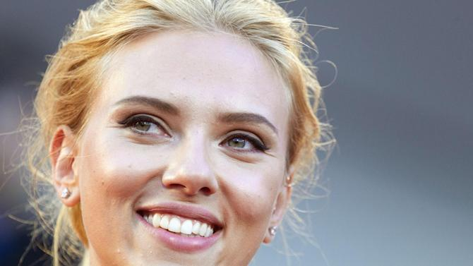 """FILE - In this Sept. 3, 2013 file photo, actress Scarlett Johansson poses for photographers on the red carpet for the screening of the film """"Under The Skin"""" at the 70th edition of the Venice Film Festival in Venice, Italy. Johansson is ending her relationship with Oxfam International after being criticized over her support for an Israeli company that operates in the West Bank. (AP Photo/Andrew Medichini, File)"""