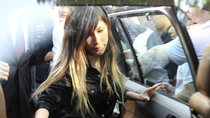 "FILE - In this Wednesday June 27, 2012 file photo, Singaporean pop music singer Ho Yeow Sun, popularly known as Sun Ho, get on a car as she leaves the Subordinate Courts in Singapore. City Harvest Church faithful queued at a Singapore court overnight and packed the public gallery to show support for the accused who prosecutors say diverted the congregation's funds into ""sham"" investments to advance the career of aspiring star Ho. Singapore opened a long-anticipated corruption trial Wednesday, May 15, 2013. (AP Photo/Wong Maye-E, File)"