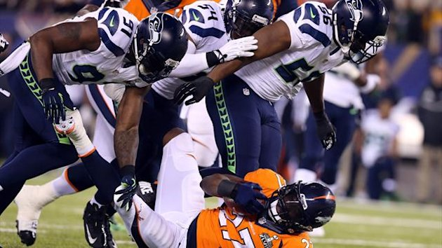 Denver Broncos running back Knowshon Moreno (27) is tackled by Seattle Seahawks defensive end Chris Clemons (91) during the first quarter in Super Bowl (Reuters)