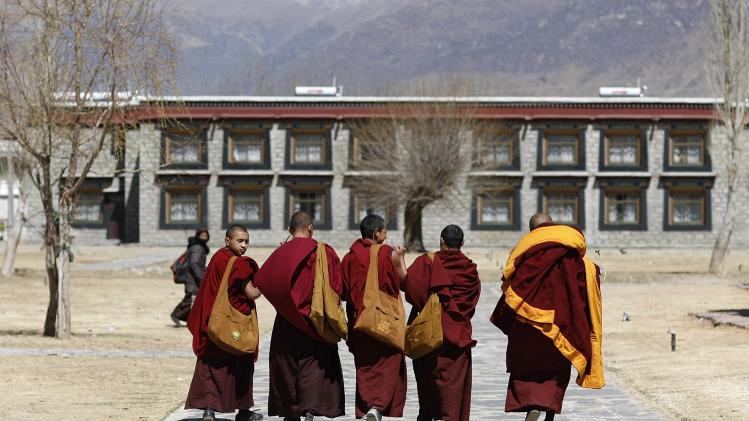 Monks walk along a street at the Samye Monastery, in Shannan Prefecture in Tibet
