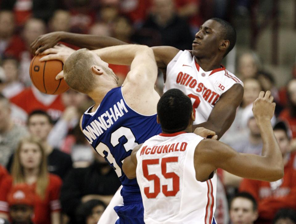 Ohio State's Shannon Scott, right, fouls UNC-Asheville's D.J. Cunningham, left, as Ohio State's Trey McDonald looks on during the second half of an NCAA college basketball game in Columbus, Ohio, Saturday, Dec. 15, 2012. Ohio State won 90-72. (AP Photo/Paul Vernon)