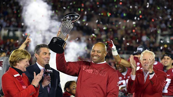 Stanford head coach David Shaw, center, lifts the trophy following their 20-14 win over Wisconsin in the Rose Bowl NCAA college football game, Tuesday, Jan. 1, 2013, in Pasadena, Calif. (AP Photo/Mark J. Terrill)