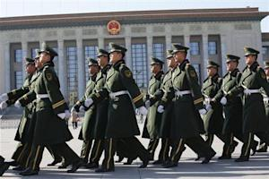 Paramilitary soldiers march as they patrol around the Tiananmen square and the Great Hall of the People where the Chinese Communist Party plenum is being held, is seen in the background in Beijing