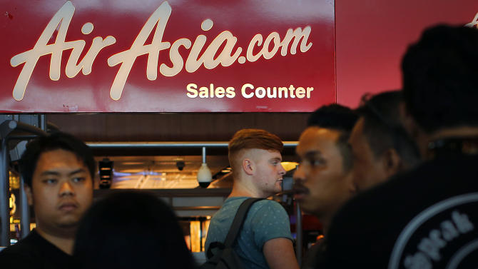 People are seen at an AirAsia service counter at the Changi International Airport on Sunday, Dec. 28, 2014 in Singapore. In the third air incident connected to Malaysia this year, an AirAsia plane with 162 people on board went missing on Sunday while flying over the Java Sea after taking off from a provincial city in Indonesia for Singapore. (AP Photo/Wong Maye-E)