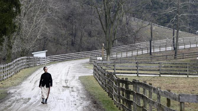 In this photo made on Tuesday, Jan. 29, 2013, a young Amish woman walks down the dirt road between the farms in Bergholz, Ohio that are worked by the families of sixteen men and women facing sentencing Friday, Feb. 8, 2013 in beard-cutting attacks on fellow Amish in Ohio. The defendants want leniency so they can return to their homes and farms, to teach their sons a trade and their daughters how to sew, cook and keep house. (AP Photo/Keith Srakocic)