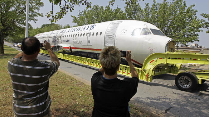 Onlookers shoot photos of the fuselage of US Airways flight 1549 as it arrives in Charlotte, N.C., Friday, June 10, 2011. The plane that made a miraculous landing on the Hudson River two years ago  will be displayed in a museum in Charlotte. (AP Photo/Chuck Burton)