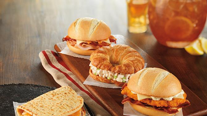 This product image provided by Dunkin' Donuts shows the chain's Grilled Chicken Flatbread, left, and bakery sandwich line. The chain has been expanding its sandwich offerings to bring in more business during the afternoon. But Dunkin' Brands CEO Nigel Travis said those sandwiches — which include fried chicken and grilled cheese varieties — shouldn't be considered lunch. (AP Photo/Dunkin' Donuts)