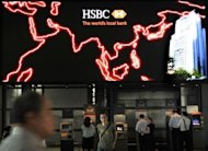 People use ATM machines at the HSBC headquarters in Hong Kong on August 1. Europe's biggest lender will slash 30,000 jobs worldwide over the next two years as part of a major cost-cutting drive aimed at refocussing on Asia, is has announced