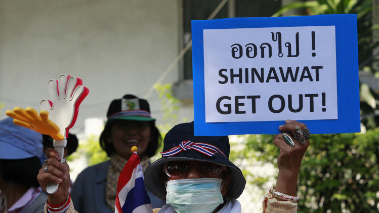 An anti-government protester uses a clapper while holding a placard during a rally on a main road leading towards the Government House in Bangkok
