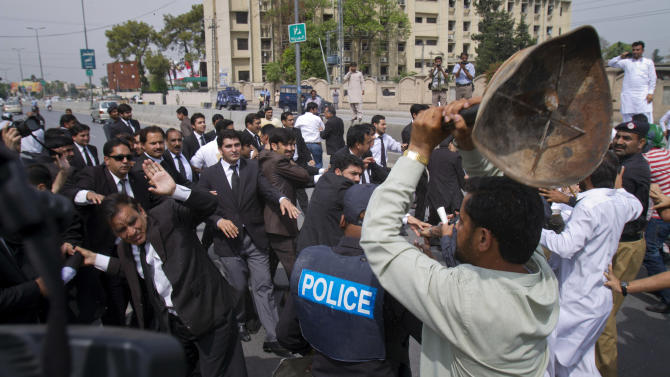 Supporters, right, of Pakistan's former President and military ruler Pervez Musharraf scuffle with lawyers outside an anti-terrorism court, where Musharraf appeared in Rawalpindi, Pakistan, Tuesday, April 23, 2013. Musharraf appeared before anti-terrorism court over the assassination of former prime minister Benazir Bhutto's case, official said.  (AP Photo/Anjum Naveed)