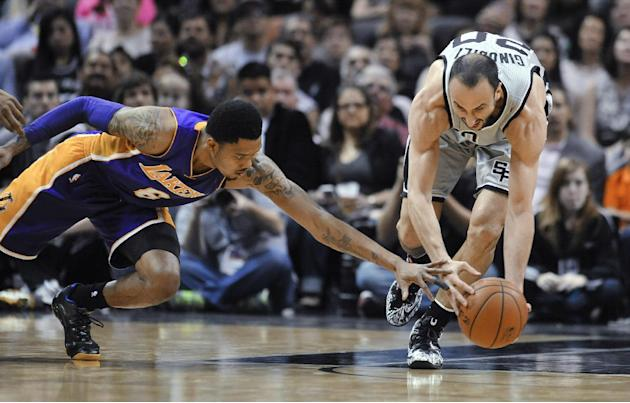 San Antonio Spurs guard Manu Ginobili, right, comes up with a loose ball in front of Los Angeles Lakers guard Kent Bazemore during the first half of an NBA basketball game Friday, March 14, 2014