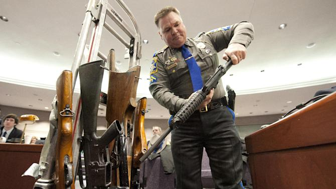 Connecticut State Trooper Joseph Delehanty unloads firearms for a demonstration during a hearing of a legislative subcommittee reviewing gun laws at the Legislative Office Building in Hartford, Conn., Monday, Jan. 28, 2013. The parents of children killed in the Newtown school shooting called for better enforcement of gun laws Monday at the legislative hearing. (AP Photo/Jessica Hill)