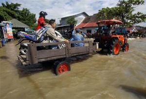 Residents sit on a loader as it makes its way down a flooded street at Srimahaphot district in Prachin Buri province