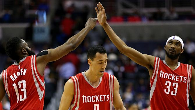 James Harden (L) and Corey Brewer (R) of the Houston Rockets high-five during a timeout in the second half against the Washington Wizards at Verizon Center on March 29, 2015 in Washington, DC
