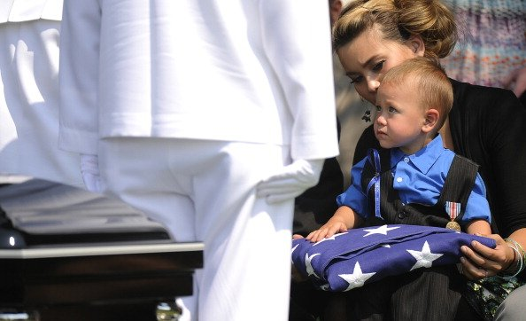 The U.S. Navy Color Guard presents the flag that adorned the casket of Jonathan Blunk to his son Maximus Blunk, 2, sitting on the lap of his mother Chantel Blunk at Mountain View Cemetery August 03, 2