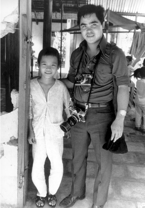 FILE - In this 1973 file photo, Phan Thi Kim Phuc, left, is visited by Associated Press photographer Nick Ut at her home in Trang Bang, Vietnam. As a nine-year-old, Kim Phuc was the subject of a Pulit