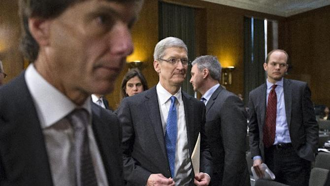 Apple CEO Tim Cook, center, is surrounded by aides as finishes his appearance on Capitol Hill in Washington, Tuesday, May 21, 2013, before the Senate Homeland Security and Governmental Affairs Permanent subcommittee on Investigations as the panel examined the methods employed by multinational corporations to shift profits offshore and how such activities are affected by the Internal Revenue Code. Lawmakers pressed Cook to learn more about Apple's tax strategies in keeping a billion dollars in an Irish subsidiary, according to a report issued this week by the subcommittee. (AP Photo/J. Scott Applewhite)