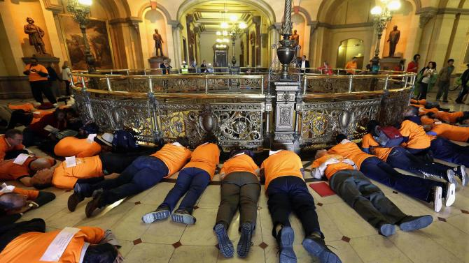 """FILE - In this April 16, 2013 file photo, members of the Community Renewal Society from Chicago participate in a """"die-in"""" protest to stop gun violence and support legislation to stop illegal gun trafficking and stronger laws for gun registration, in front of Illinois Gov. Pat Quinn's office at the Illinois State Capitol in Springfield. As Quinn mulls whether to sign off on eliminating the nation's last ban on public possession of guns, the question in Chicago is whether it will matter in the crime-weary city where a spiking murder rate drew national attention last year. (AP Photo/Seth Perlman, File)"""