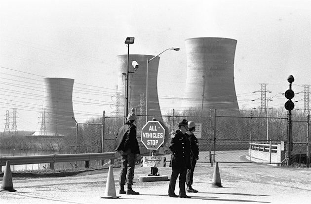 FILE - In this Wednesday, March 28, 1979 file photo, a Pennsylvania state police officer and plant security guards stand outside the closed front gate to the Metropolitan Edison nuclear power plant on Three Mile Island near Harrisburg, Pa. after the plant was shut down following a partial meltdown. The plant's cooling towers are seen in the background. The U.S. government has adopted the first set of comprehensive changes in the emergency planning program for communities near nuclear power plants since its creation after the Three Mile Island accident in 1979. In revisions which went into effect on December 2011, the U.S. government is allowing communities within 50 miles of nuclear power plants to practice less often for major accidents and is recommending that far fewer people who live nearby be evacuated immediately. Under new emergency planning rules, federal regulators also are ending a requirement that emergency personnel always practice for a release of radiation. (AP Photo/Paul Vathis)