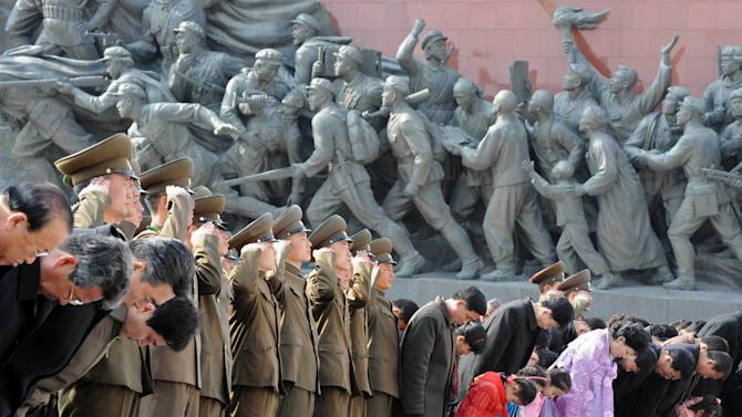 Military personnel salute as civilians bow to giant statues of the late North Korean leaders, Kim Il Sung and his son Kim Jong Il, unseen, in Pyongyang, North Korea, Monday, April 15, 2013. Oblivious to international tensions over a possible North Korean missile launch, Pyongyang residents spilled into the streets Monday to celebrate a major national holiday, the birthday of their first leader, Kim Il Sung. (AP Photo/Kyodo News) JAPAN OUT, MANDATORY CREDIT, NO LICENSING IN CHINA, HONG KONG, JAPAN, SOUTH KOREA AND FRANCE