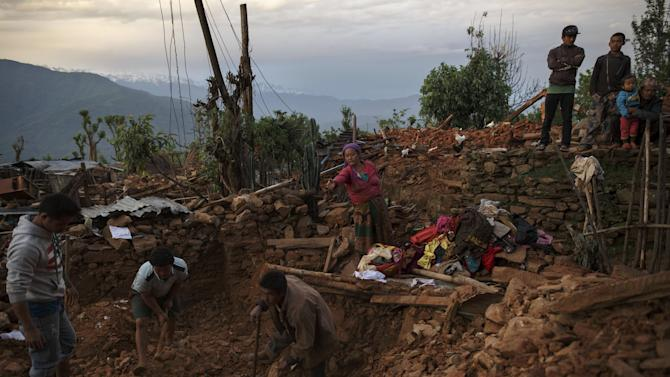 Local villagers try to salvage their belongings from the debris of their house at a devastated area following Saturday's earthquake, at Paslang village in Gorkha