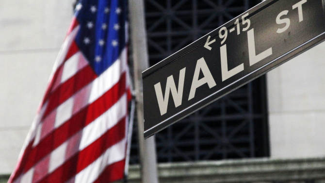 FILE - This Monday, July 15, 2013 file photo shows the American flag and Wall St. street sign outside the New York Stock Exchange, in New York. European and Asian stocks rose Tuesday, July 29, 2014 ahead of a string of U.S. and Chinese economic reports later this week and despite the possibility of more sanctions on Russia. Wall Street was expected to rise on the open. (AP Photo/Mark Lennihan, File)