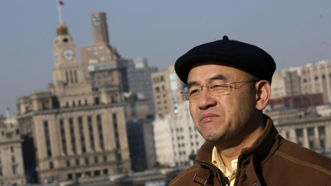 In this Jan. 28, 2013 photo, Chinese-born U.S. scientist Hu Zhicheng stands at the waterfront promenade along the Huangpu River in Shanghai, China. Hu, who was held in China for nearly five years after he became involved in a dispute with a competitor has been allowed to return to his Southern California home, his wife said Tuesday, June 4, 2013. (AP Photo/Eugene Hoshiko, File)