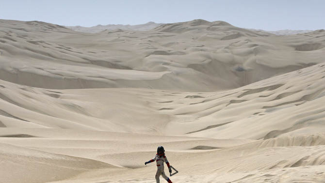 Jan. 13 Erik Wevers, Dutch co-driver of the Mitsubishi driven by Fabian Lurquin, from Belgium, walks along the desert after their car got stuck in the sand during the 12th stage of the 2012 Argentina-Chile-Peru Dakar Rally between Arequipa and Nazca in Peru, Friday, Jan. 13, 2012. (AP Photo/Martin Mejia)