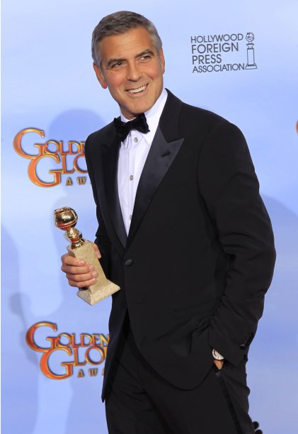 "George Clooney poses with his award for best actor in a motion picture - drama for ""The Descendants,"" backstage in Beverly Hills"