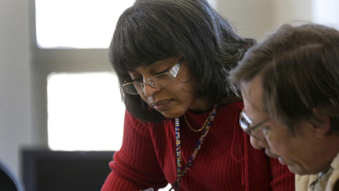 Caseworker Cheryl Boone helps a client with paperwork during a therapy session at the Johnson County Mental Health Center Wednesday, Jan. 23, 2013, in Shawnee, Kan. Lawmakers across the nation are rethinking cuts in mental health care spending in the wake of recent shootings. (AP Photo/Charlie Riedel)