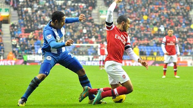 Arsenal's Theo Walcott (right) is fouled in the penalty area by Wigan Athletic's Jean Beausejour (PA Sport)