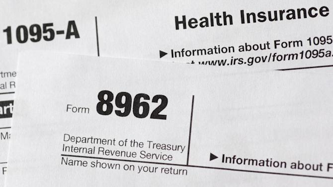 This Aug. 21, 2014, photo shows health care tax forms 8962 and1095-A, in Washington. Who thinks about taxes around Labor Day? If you value your tax refund and you're one of millions getting a health insurance tax credit under President Barack Obama's health care law, it's not too early. If you worked a lot of overtime, or maybe your spouse got a higher-paying job, arcane connections between the health law and taxes can reduce or even eliminate your refund. (AP Photo/Carolyn Kaster)