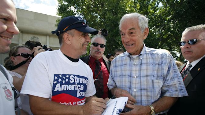 U.S. Rep. Ron Paul, R-Texas, signs an autograph during the Iowa Republican Party's Straw Poll, Saturday, Aug. 13, 2011, in Ames, Iowa. (AP Photo/Charlie Neibergall)