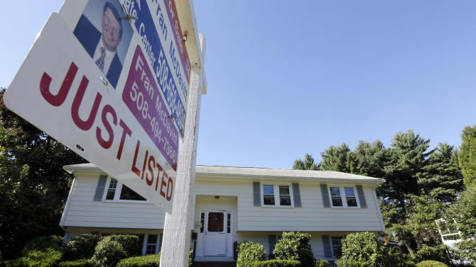 In this Wednesday, Sept. 18, 2013 photo a for sale sign hangs in front of a house in Walpole, Mass. Freddie Mac reports on mortgage rates for this week on Thursday, Sept. 26, 2013.( AP Photo/Steven Senne)