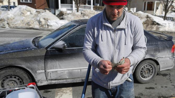 Mack Donohue, who has been homeless since 2008, counts his money from tips from cleaning drivers' windshields in Boston
