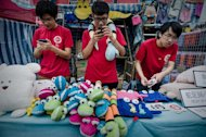 Young sales assistants are seen at a stall of a Chinese New Year fair in Hong Kong, on February 5, 2013. The Lunar New Year will mark the year of the snake on February 10
