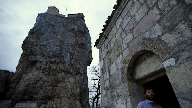 A man attends a service near the church on top of the Katskhi Pillar, a rock mass about 40 meters high, in the village of Katskhi