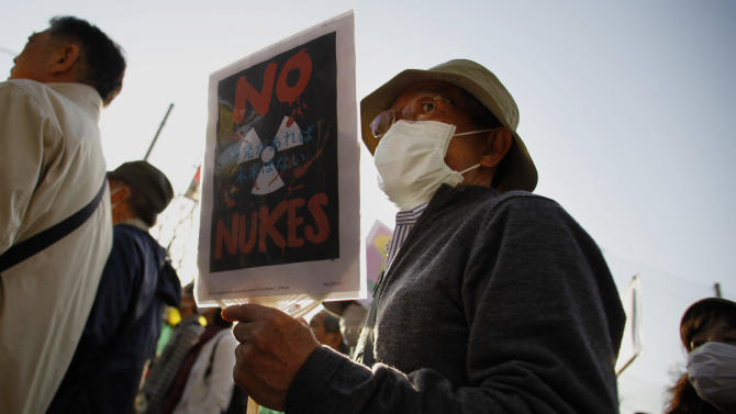 A protester holds a placard during an anti-nuclear demonstration in Tokyo, Saturday, March 9, 2013. Gathering on a weekend ahead of the second anniversary of the March 11 quake and tsunami that sent Fukushima Dai-ichi plant into multiple meltdowns, demonstrators said they would never forget the world's worst nuclear catastrophe, and expressed alarm over the government's eagerness to restart reactors. (AP Photo/Junji Kurokawa)