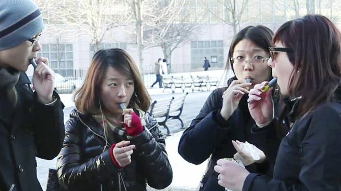 FILE - In this Monday, Jan. 23, 2012 still file photo taken from video, students try free samples of AeroShot, an inhalable caffeine packed in a lipstick-sized canister, on the campus of Northeastern University in Boston. The Food and Drug Administration will investigate the safety and legality of the product created by Harvard biomedical engineering professor David Edwards. (AP Photo/Rodrique Ngowi, File)