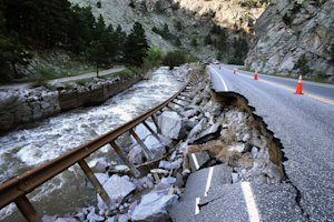 A guardrail hangs away from a closed canyon road, which…